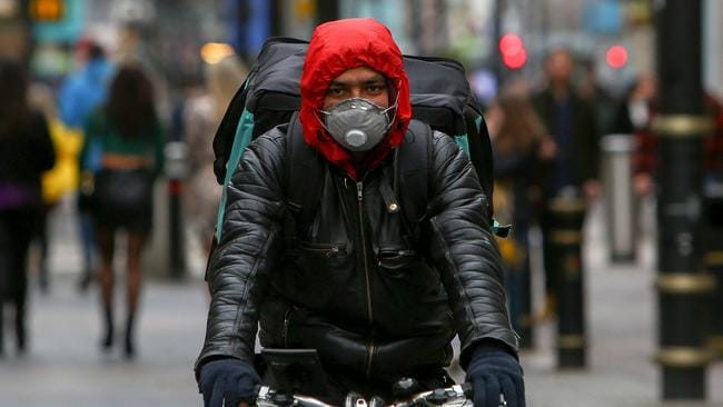 A delivery man wearing a mask cycles in Cardiff, Wales on March 14, 2020. Picture: Geoff Caddick/AFP