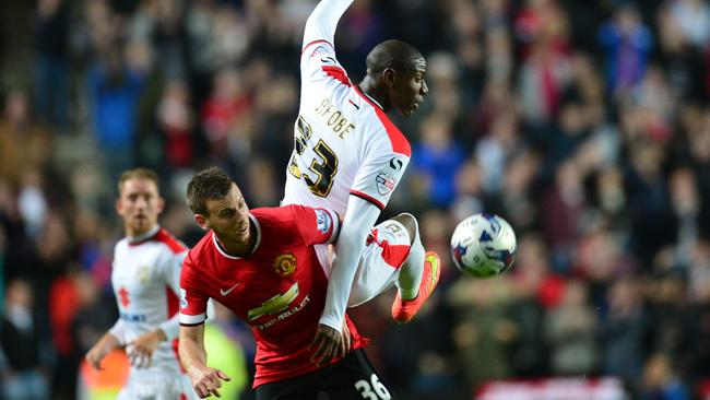Manchester United defender Marnick Vermijl vies with MK Dons English striker Benik Afobe
