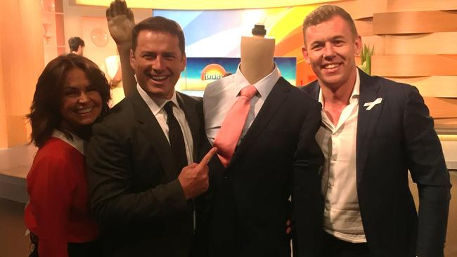 The suit's winning bidder Rohan Gull collects the 'stanky' suit from Today's Karl Stefanovic and Lisa Wilkinson.