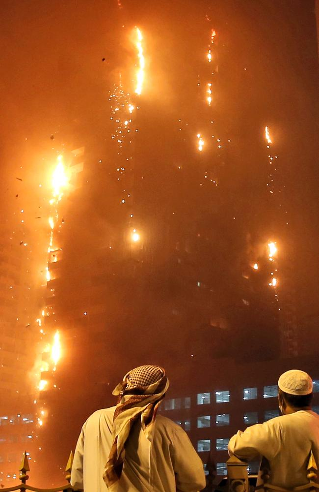 Two Emirati officials watch as a fire spreads up the side of a high-rise building in Ajman.
