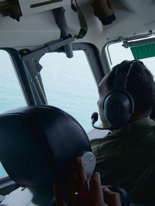 An Indonesian Navy Pilot looks out the cockpit window as he banks to check out an object sighted during a search of the waters near Bangka Island. Picture: Ed Wray
