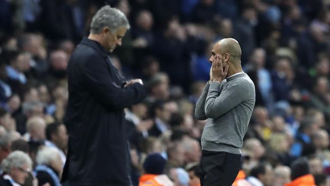 Manchester United manager Jose Mourinho, left, checks his watch next to Manchester City coach Pep Guardiola