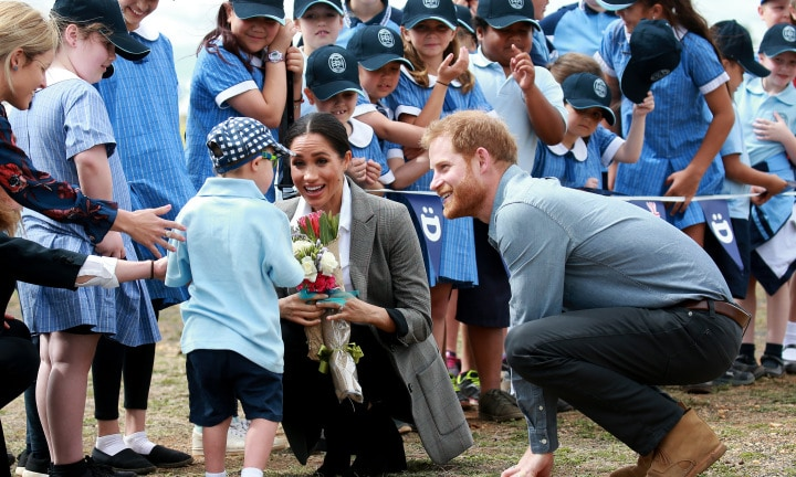 POOL PHOTOS - The Duke and Duchess of Sussex, Prince Harry and Meghan Markle visit the drought affected area of Dubbo in central west NSW, visiting the Royal Flying Doctor Service and local drought affected farmers. Buninyong Public School student Luke Vincent gives Harry and Meghan a hug. Picture: Toby Zerna