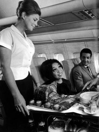 A flight attendant serves roast dinner to first-class passengers on a British Overseas Airways Corporation flight in 1964.