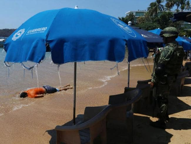 The body washed up just metres from tourists. Picture: Reuters