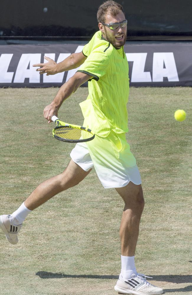 Jerzey Janowicz of Poland returns the ball to Grigor Dimitrov.