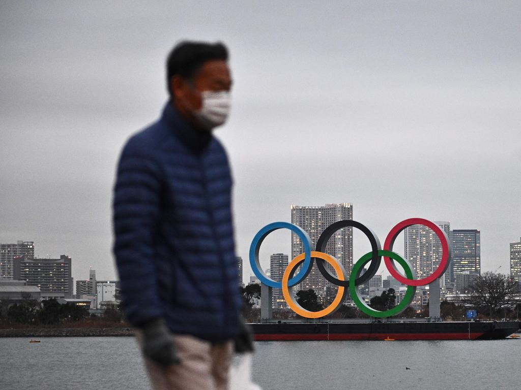 A man walks past the Olympic rings on display at the Odaiba waterfront in Tokyo.