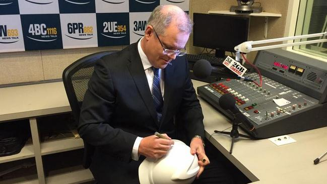 Before his heated exchange on 2GB, Scott Morrison signed a hard hat that will be auctioned for charity. Picture: Twitter / Stephanie Borys