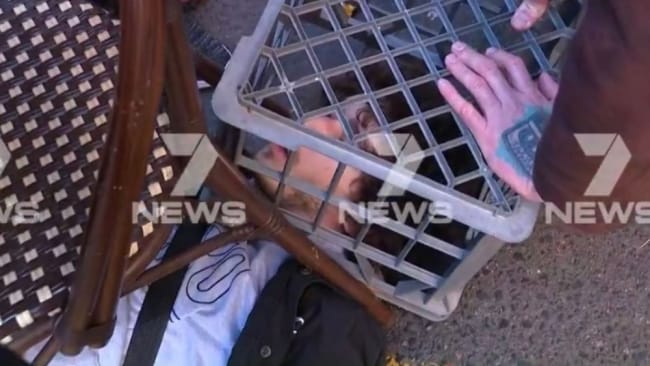 The man was held down with a milk crate as police arrived. Image: 7 News