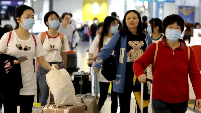 Travellers from Shanghai arriving last week at Sydney Airport don masks as they emerge from customs. Picture: Chris Pavlich.