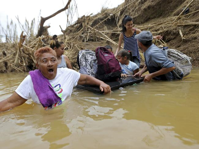 Marta Sostre Vazquez reacts as she starts to wade into the San Lorenzo Morovis River with her family in Morovis, Puerto Rico on Wednesday, September 27, after a bridge was swept away by Hurricane Maria. The family was returning to their home after visiting family on the other side. Picture: Gerald Herbert/AP
