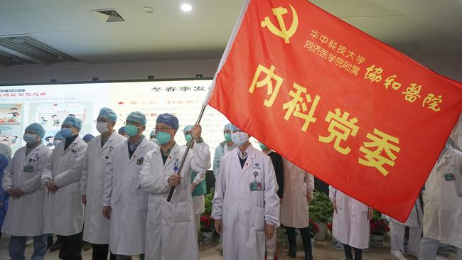 "Medical workers in Wuhan participate in a ceremony to form an ""assault team"" to battle against a coronavirus epidemic. Picture: Cheng Min/Xinhua via AP"