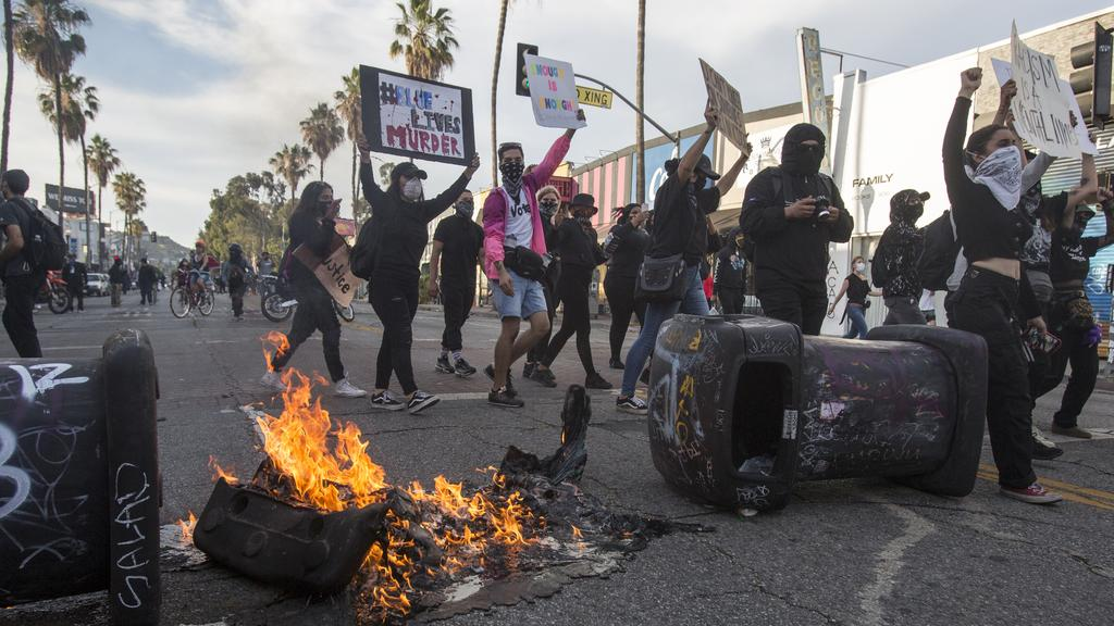 Protesters march by the burning trash cans during a protest over the death of George Floyd, a handcuffed black man in police custody in Minneapolis, in Los Angeles, Saturday, May 30, 2020. Picture: Ringo H.W. Chiu/AP