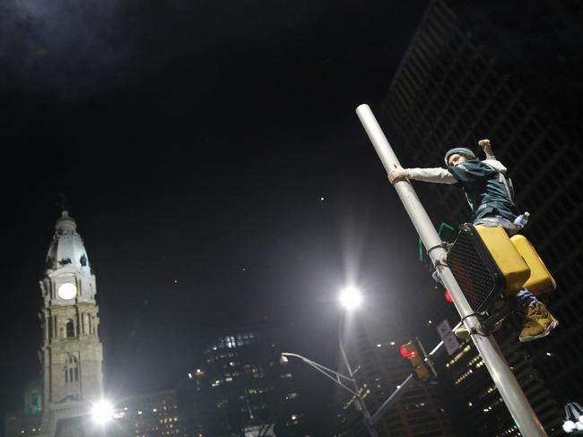 A fan celebrates in Center City, atop a traffic light.