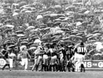 As the crowd huddles against the rain, a fight breaks out during the Port vs Glenelg semi-final at Football Park in 1977.