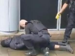 Police hold a man to the ground outside a shopping centre in Manchester England where five people were stabbed. Picture: Twitter