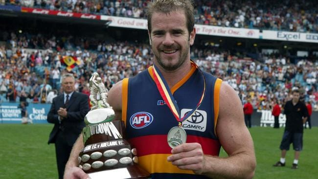 Mark Ricciuto shows off the trophy and medal after the Crows won Showdown XVII.