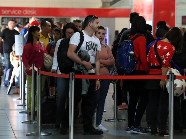 Security at Brisbane Airport has also been increased after a foiled terror plot in Sydney. Passengers queue to get through security on Sunday. Picture: Adam Head