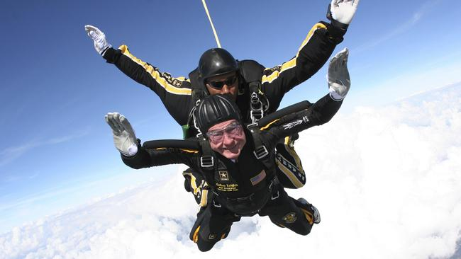 November 2007: George H.W. Bush free falls with Golden Knights parachute team member Sgt. 1st Class Mike Elliott, as he makes a dramatic entrance to his presidential museum. Picture: AP
