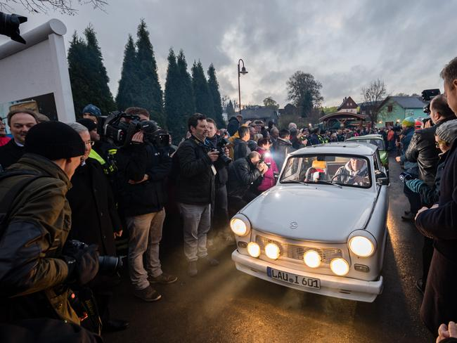 People arrive in East German-era Trabant cars at a former border crossing to recreate scenes from 30 years ago when East Germans lined up to drive into the West. Picture: Jens Schlueter/Getty Images.