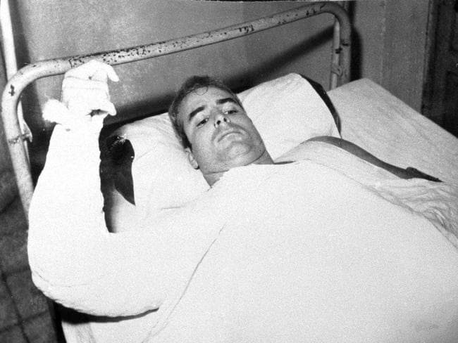 John S. McCain, is seen lying injured in North Vietnam wearing an arm cast. Picture: AFP
