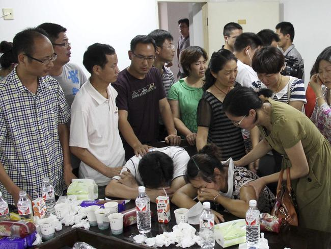 Parents of Wang Linjia, centre, are comforted.