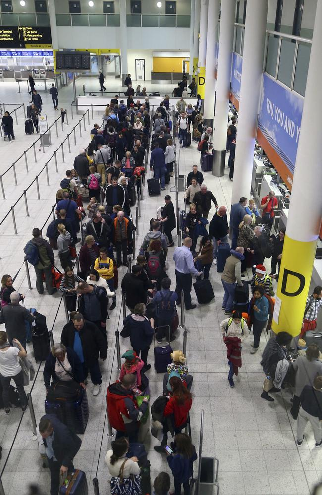 Passengers queue for flights at Gatwick Airport as the airport and airlines work to clear the backlog of flights delayed by a drone incident earlier in the week. Picture: AP