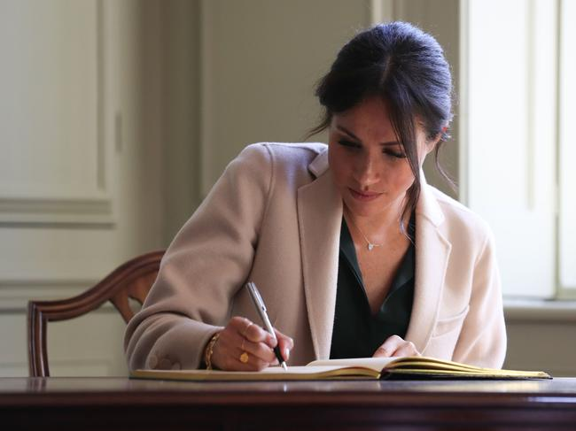 Meghan, Duchess of Sussex signs the visitors book during an engagement at Edes House.