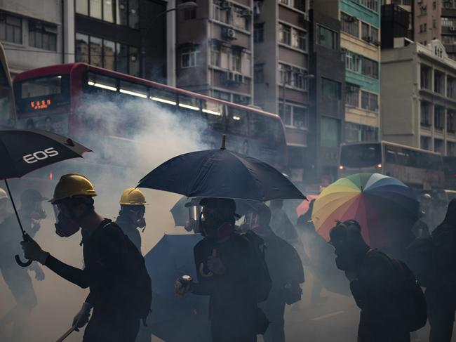 Protesters face tear gas fired by police in Hong Kong, ignoring a ban on the rally. Picture: AP