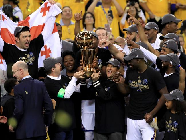 The Golden State Warriors celebrate with the Larry O'Brien Trophy.
