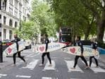 Climate change campaigners in wetsuits holding surfboards cross the road by the Houses of Parliament in London on, ahead of a mass lobby to urge members of parliament to back strong action on climate change. AFP PHOTO / JUSTIN TALLIS