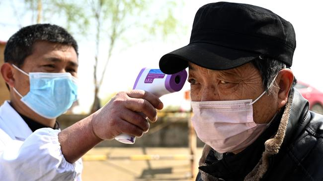 A passenger has his temperature checked before commuting on a boat in Jiujiang across the Yangtze river. Picture: AFP