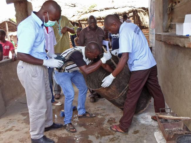 Mozambique officials gather samples from a drum that was used to brew the beer.