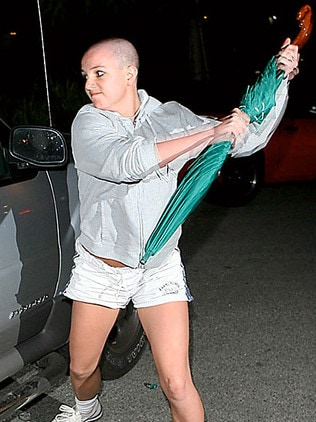Spears attacking paparrazo's car with umbrella.