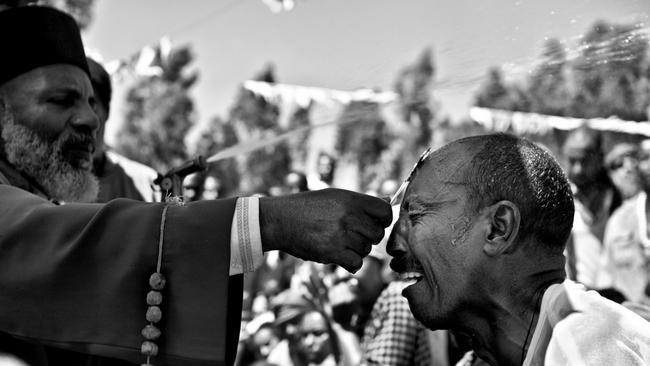 A man cries during the ceremony as holy water sprays above his head. Picture: David Tesinsky