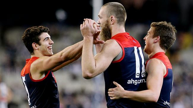 Max Gawn celebrates with Christian Petracca and Jack Trengove.