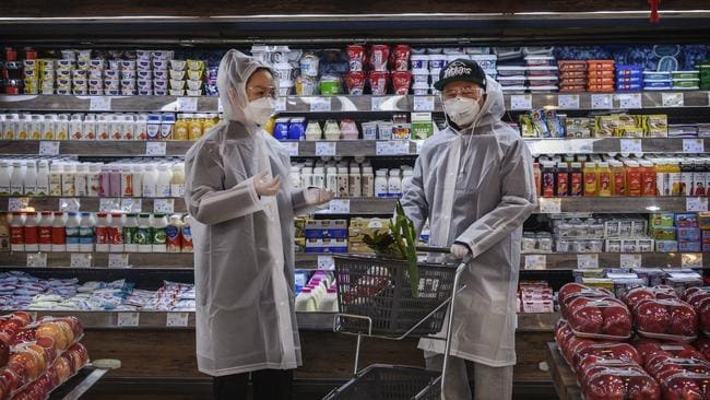 A Chinese couple wear plastic coats and protective masks as they shop for groceries at a supermarket in Beijing, China. Picture: Kevin Frayer/Getty Images