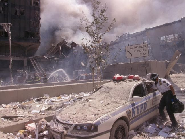 A police officer reaches into a debris and ash-covered police car in lower Manhattan. Picture: Alamy