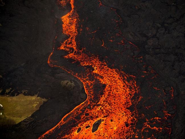 Lava from the Kilauea volcano erupts from a fissure and forms a river of lava flowing down to Kapoho on June 10. Picture: AP/LE Baskow