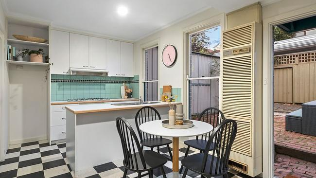 The black and white chequered kitchen and dining room opens to the backyard.
