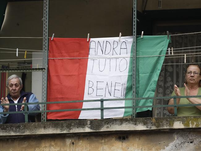 A couple applauds next to an Italian flag reading everything will be all right, at the Garbatella neighbourhood, in Rome. Picture: AP