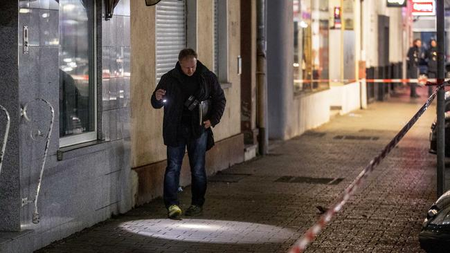 A police officer looks for evidence outside a restaurant. Picture: Michael Probst/AAP