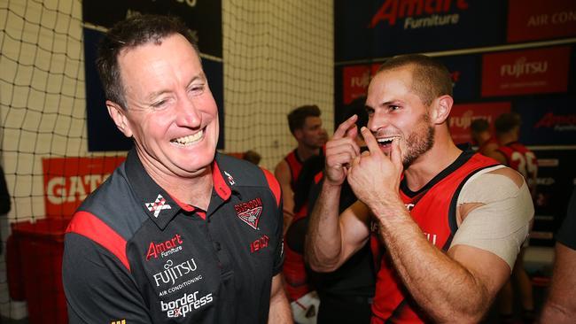 Essendon's David Zaharakis celebrates the Round 3 win over Melbourne with Bombers senior coach John Worsfold.