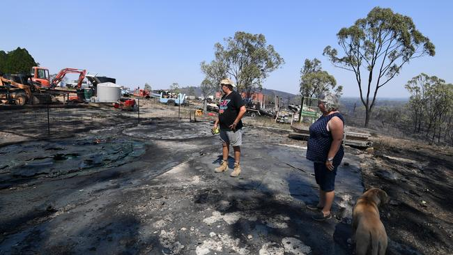Nick and Jeanette Schwindt inspect their burnt out water tanks after a bushfires swept through the area in Mount Larcom, Queensland. Picture: AAP/Dan Peled