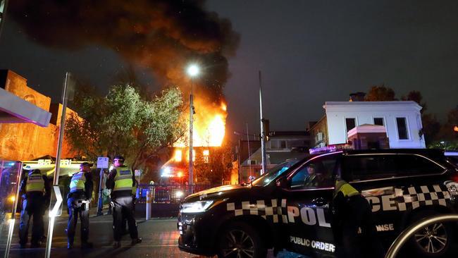 A polícia chega ao local, enquanto o Teatro La Mama, em Melbourne, queima no fundo. Foto: Patrick Herve.