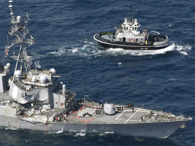 The crushed side of the USS Fitzgerald as the destroyer limps back to Yokosuka, home base of the 7th Fleet, beside a US tugboat. Picture: Kyodo News / AP