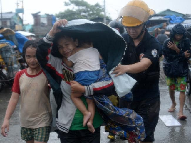 Get out ... A fireman helps a mother and her child evacuate from their house at an informal settlers' area as Typhoon Rammasun barrels across Manila. Pic: TED ALJIBE