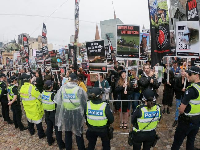 A line of police officers stood in front of the protesters as they held signs and chanted at the passing parade. Picture: Mark Evans/Getty Images