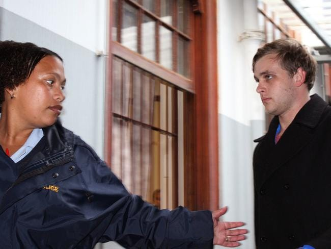 Henri van Breda, right, is led by a South African police woman during a court appearance last year. Picture: AP Photo/Danie Keet, Eikestadnuus