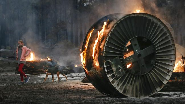Jessica Tregellas walks her dog past a burning NBN cable spool. Picture: David Caird